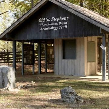 a cabin in the woods with a sign on the front that reads Old Saint Stephens Where Alabama Began Archaeology Trail